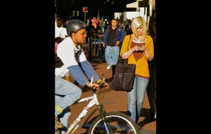 Blonde_woman_with_tattoos_texting_on_streetskycrop