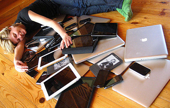 Woman cuddling with multiple digital devices